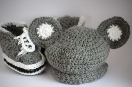 Handmade knitted baby bootees and a hat Stock Photo