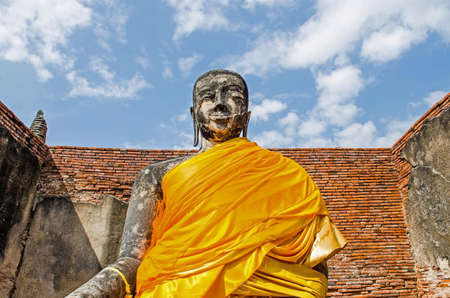 Robe: Buddha statue with Yellow robe in the old sanctuary, Thailand Stock Photo