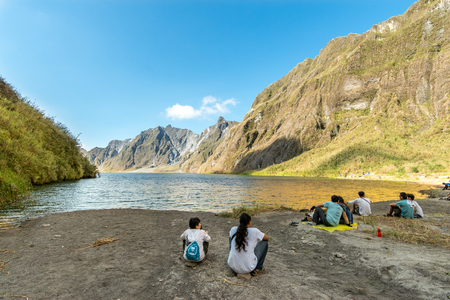 Feb 18,2018 Tourists and guides taking a break in front of Mt. Pinatubo crater lake, Capas, Philippines