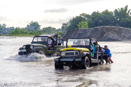 CAPAS , PHILIPPINES - July 8, 2018 : People pushing cars in the river Editorial