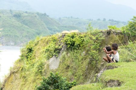 Children sitting on a hill at Mt.Pinatubo, Philippines