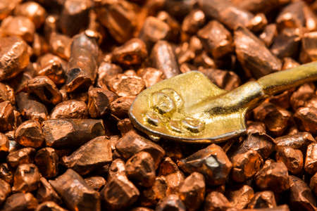 Tiny shovel in the hill of copper ore Stock Photo