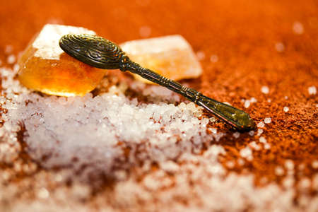 Tea spoon on the sweet crystal of sugar at a light brown background
