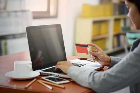 Asian business women pay for purchases using credit cards. During a laptop computer in the office. Finance, Banking and Technology Concepts. Stock Photo