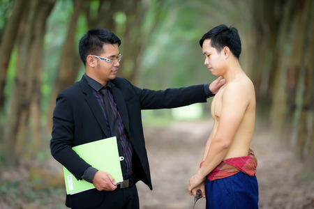 Close up Businessmen are admiring vegetable gardeners for planting rubber trees. Stock Photo