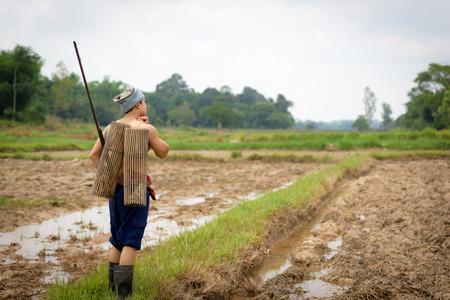 Male farmer carrying a rifle walks along.