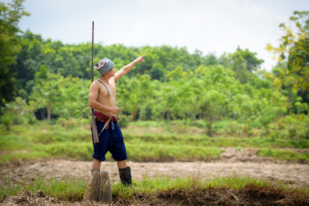 Male farmer carrying a rifle walks along and pointing to the sky
