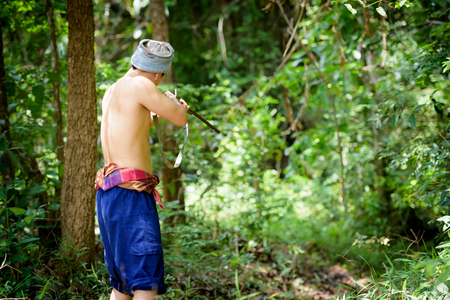Asian man farmer aiming gun a rifle walks along in the forest background. Hunting and the way of life of rural people in Thailand concept.
