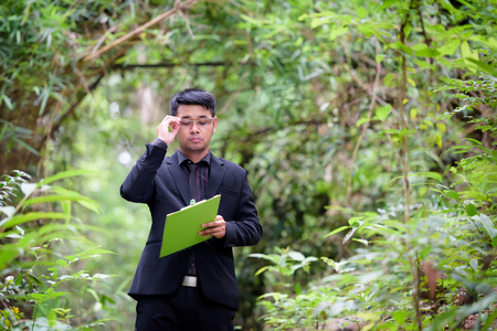 Plant researchers are checking the paper in a forest. Stock Photo
