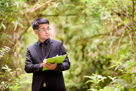 Plant researchers are checking the paper in a forest.