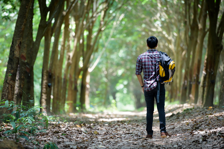 Happy Asian man backpack in the rubber plantation background. Travel and holiday concept. Stock Photo