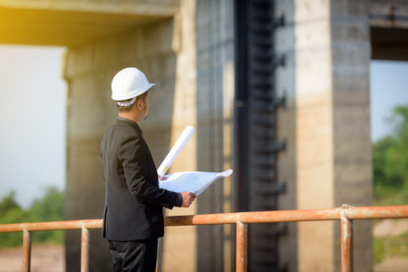 Asian young man engineers are holding a blueprint and looking to the floodgates for check progress of the  construction project. Industry and Business Concepts.