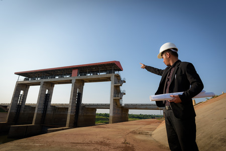 Engineers are holding a blueprint and point fingers to the floodgates.