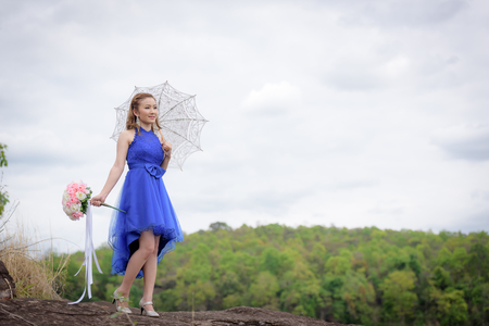 Beautiful woman wear blue evening dress hold a bouquet of flowers and white umbrella. over mountains and rivers background.