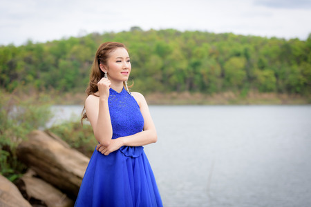 Beautiful woman wear blue evening dress over mountains and rivers background. Stock Photo