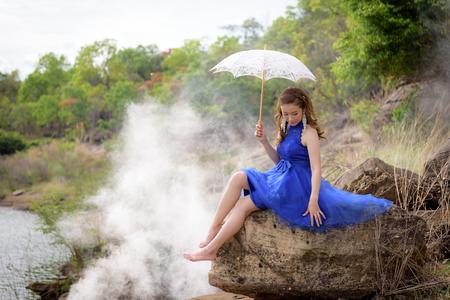 Beautiful woman wear blue evening dress hold white umbrella on the rocks.