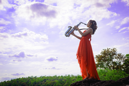 Beautiful woman wear red evening dress sound saxophone stand on the rocks over mountains and rivers background.