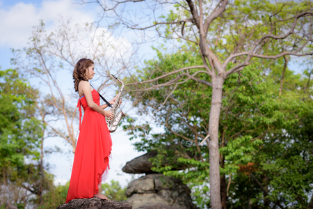 Beautiful woman wear red evening dress holding saxophone stand on the rocks.