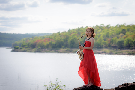 thai musical instrument: Beautiful woman wear red evening dress holding saxophone stand on the rocks over mountains and rivers background. Stock Photo