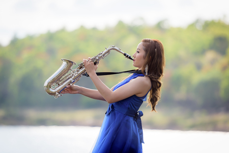 thai musical instrument: Beautiful woman wear blue evening dress sound saxophone over mountains and rivers background.