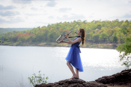 thai musical instrument: Beautiful woman wear blue evening dress sound saxophone stand on the rocks over mountains and rivers background.