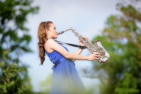 Beautiful woman wear blue evening dress sound saxophone over mountains and rivers background.