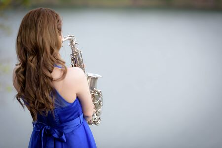 tercet: Close up Beautiful woman wear blue evening dress sound saxophone over mountains and rivers background.