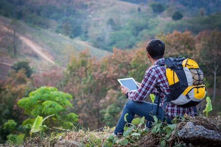 Tourists look at a map on the tablet on mountain.