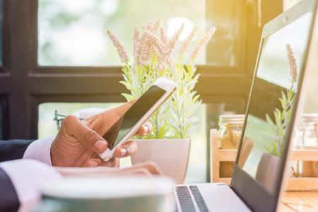 Zakenman met behulp van draagbare laptop terwijl u in de koffiewinkel zit. Stockfoto