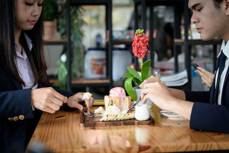 Beautiful Asian businesswoman and businessman eating ice cream bread topped with honey on a wooden table in a coffee shop. Food, drinks and business concepts.