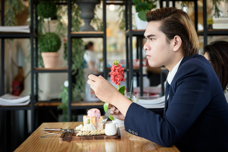Asian businessman eating ice cream bread topped with honey on a wooden table in a coffee shop. Food, drinks and business concepts.