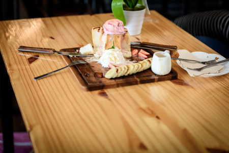 Ice cream pie topped with honey on a wooden table in a coffee shop. The picture is after being eaten.