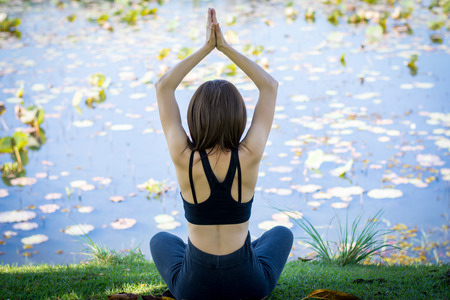 Woman practicing yoga on the lawn near the pool. Stock Photo