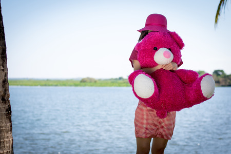 Happy woman standing with doll on the grass near the river. Stock Photo
