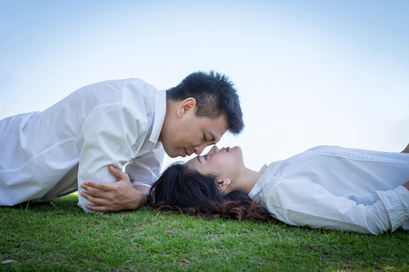 Man kissing young woman on the grass.