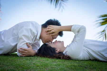swain: Man kissing young woman on the grass.