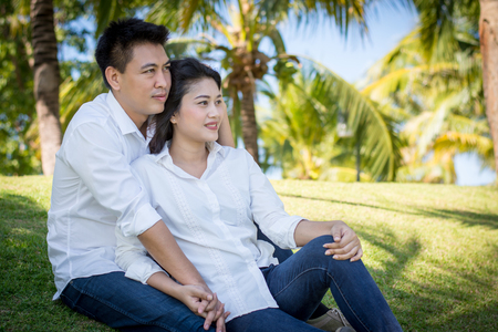 Young happy lovely couple sitting in the green park. Stock Photo
