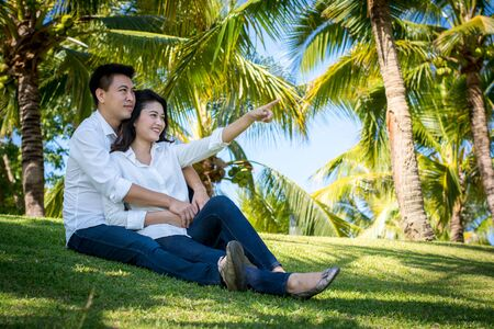 valued: Young happy lovely couple sitting in the green park. Stock Photo