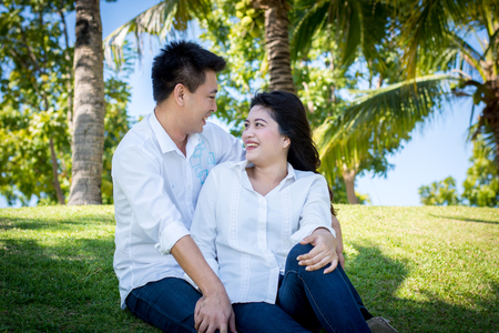 swain: Young happy lovely couple sitting in the green park. Stock Photo