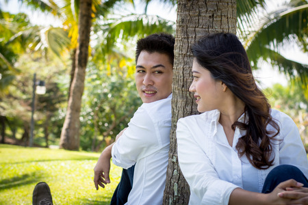 swain: Young happy lovely couple sitting in the green park. Man look at young woman under the coconut tree.
