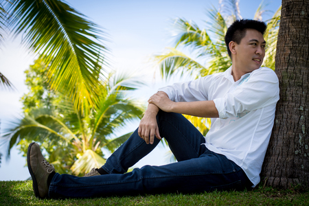 Men wear white shirts sit under the coconut trees.