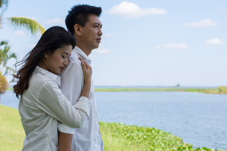 swain: Beautiful Young couple with white coats standing on a green lawn. Woman hugging man.