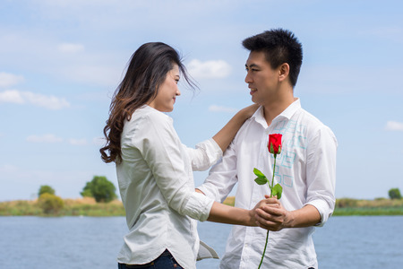 Beautiful Young couple with white coats standing on a green lawn. Man hugging young woman holding a red rose.