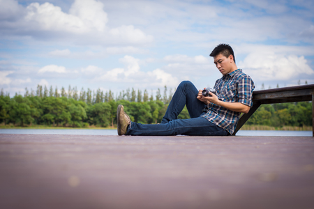 Hipster man sitting on the lake pier with holding vintage camera, Relaxed atmosphere, summer. Stock Photo