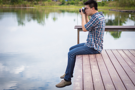 he: Hipster man sitting on the lake pier with holding vintage camera, Relaxed atmosphere, summer. Stock Photo