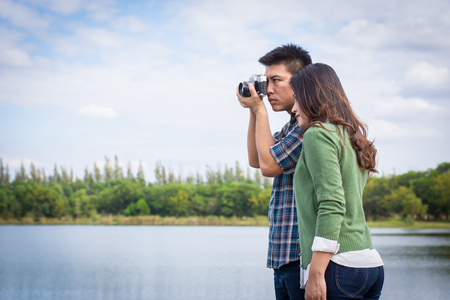 Young men and young women Couple together standing on bench waterfront port in the park. Handle vintage camera. Stock Photo