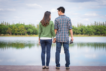 Beautiful Young couple with green coats standing hand in hand on bench waterfront port in the park. Stock Photo