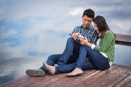 Young men and young women Couple together sitting on bench waterfront port in the park. Handle vintage camera.