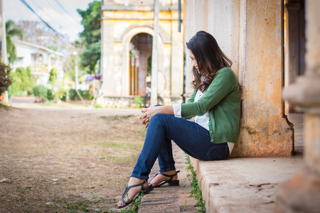 mournful: Depressed women. Asian beautiful girl sits sadly on the cement floor in ancient houses.