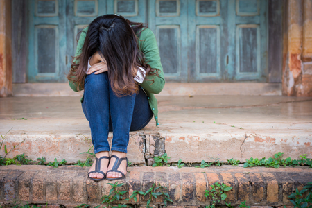 structuring: Depressed women. Asian beautiful girl sits sadly on the cement floor in ancient houses.